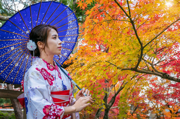 Wall Mural - Asian woman wearing japanese traditional kimono with umbrella in autumn park. Japan
