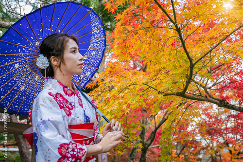 Wall mural Asian woman wearing japanese traditional kimono with umbrella in autumn park. Japan