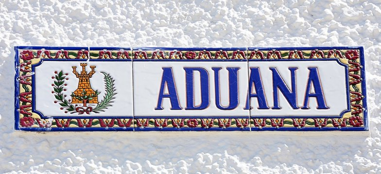 Ceramic customs (Aduana) sign on a building along the waterfront, Ayamonte, Spain.