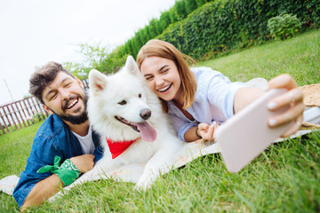 Couple with dog. Young couple lying on the grass making photo with their dog while having traditional picnic