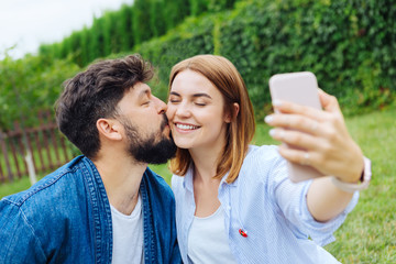 Selfie with man. Beaming blonde-haired woman feeling extremely happy while making selfie with her man
