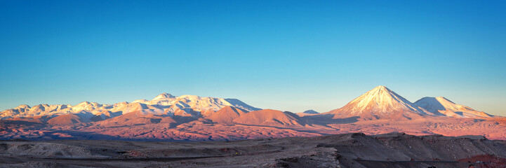 Panorama of Moon Valley in Atacama desert at sunset, snowy Andes mountain range in the background, Chile