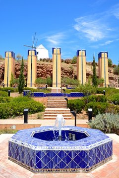 Modern blue tiled fountain at the top of the hill with a traditional white windmill to the rear, Castro Marim, Algarve, Portugal.