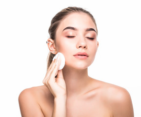 Gorgeous girl with nude make up and naked shoulders posing at grey background with cleaning sponge. Skin care concept.