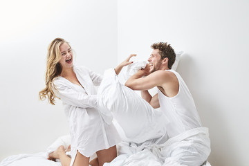 Young couple pillow fighting in bedroom