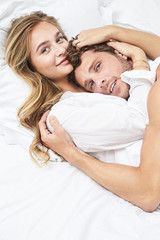 Embracing young couple in bed, portrait