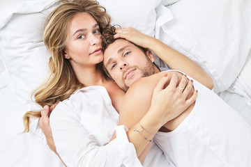 Young couple relaxing in bed, portrait