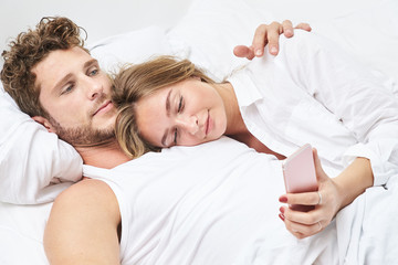 Young woman using Smartphone in bed with boyfriend