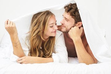 Loving young couple under bed sheet
