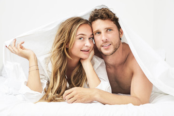 Young couple in bed under sheet