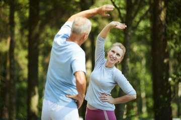 Senior active couple doing side-bends in natural environment while standing in front of each other