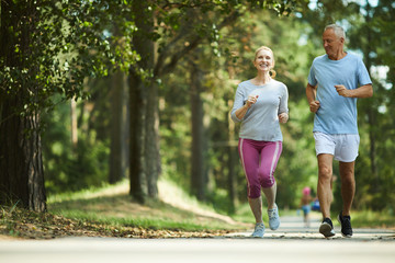 Poster Jogging Active and healthy aged couple running in natural environment on summer morning