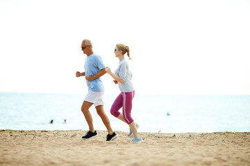 Active senior spouses jogging along coastline on sandy beach in the morning