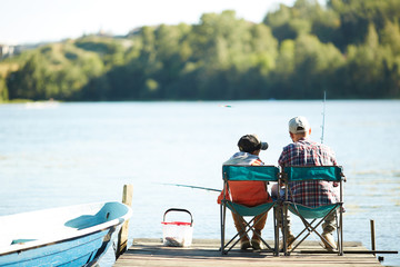 Father together with his son catching fish in the lake using fishing rod