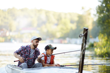 A father teaching his son how to fish on the lake outside in summer day