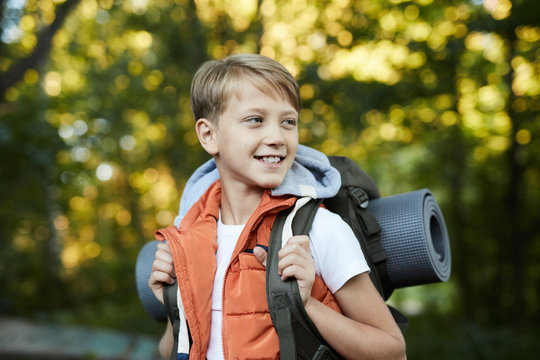 Young happy boy walking with backpack, having fun in summer forest