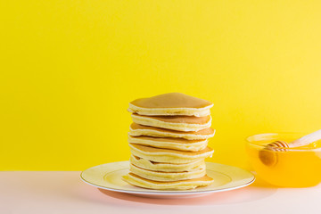 Pancakes with honey on a yellow pink background. Appetizing pancakes on a white plate and honey....