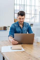 mann sitzt am schreibtisch im büro und schaut auf sein notebook