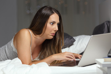 Confused woman reading email at home