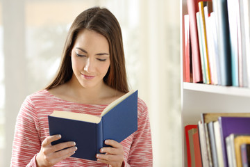 Woman reading a book standing at home