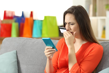 Worried lady buying online with credit card and phone