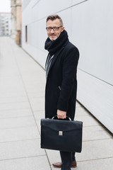 Smiling mature man standing with briefcase