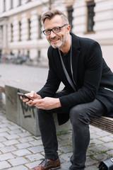 eleganter mann sitzt in der stadt auf einer bank und hält sein smartphone in der hand