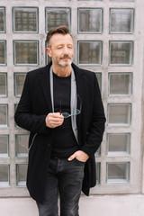 mann im mantel steht in der stadt vor einer glasfassade und schließt die augen