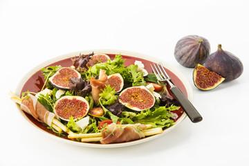 gemischter Blattsalat mit Feigen, Tomaten, Schafskaese und Crossinis mit Schinken auf roten Teller, Freisteller