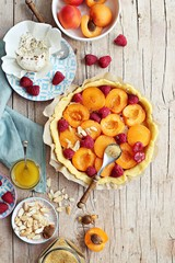 Tart with apricots and raspberry. Summer berries dessert. Overhead view.