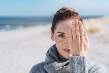 Serious woman on a beach covering one eye