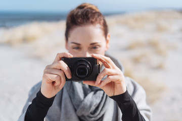 Attractive woman tourist taking photos on a beach