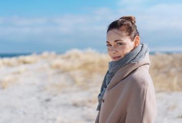 Attractive woman on a sunny sandy winter beach