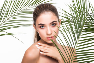 Portrait of young beautiful woman with a palm leaf, clean skin, Skin care concept.