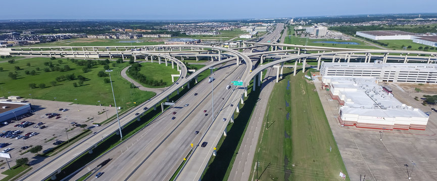 Panorama top view Interstate 10 or Katy freeway massive intersection, stack interchange, elevated road junction overpass in daytime with clear blue sky. Aerial metropolitan area of Katy, Texas, US