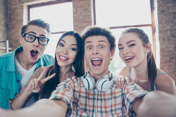 Group of youngsters make fooling selfie on the phone from a cafe from a trip on an excursion to another city