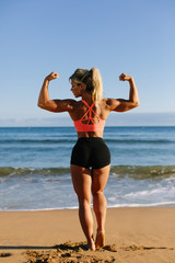 Fitness young woman flexing biceps at the beach