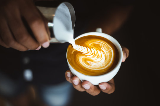 Barista making a cup of coffee latte art.