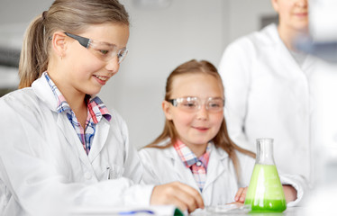 education, science, chemistry and children concept - kids or students with test tube making experiment at school laboratory