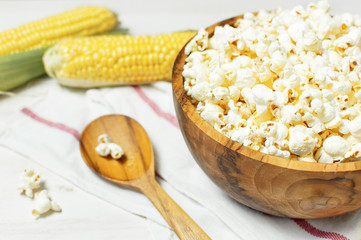Brown wooden bowl with delicious traditional popcorn, fresh corn and a spoon on a light wooden background. Top view of a light meal background.