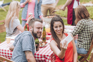 A young couple taking a selfie photo at a weekend BBQ party outside.