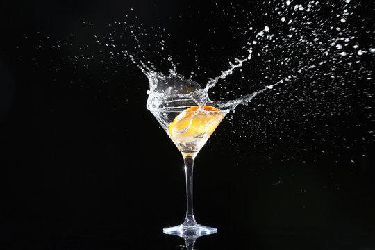 Glass with splashing cocktail and slice of orange on black background