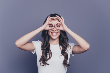 Attractive nice pretty charming adorable stylish cheerful curly-haired foolish girl in casual white t-shirt, showing like glasses gesture, isolated over grey background