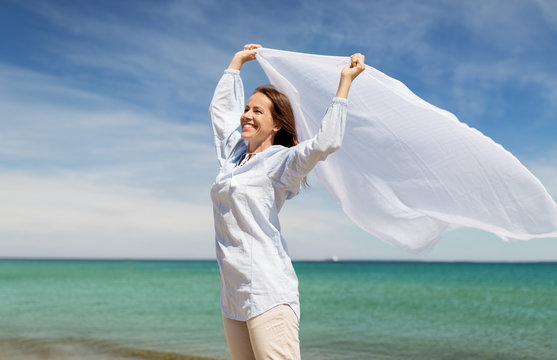 people and leisure concept - happy woman with shawl waving in wind on summer beach