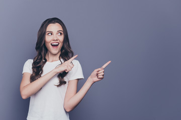 Portrait of magnificent lovely adorable stylish cheerful delighted curly-haired girl in casual white t-shirt, pointing aside up with two hands, opened mouth, copy-space, isolated over grey background