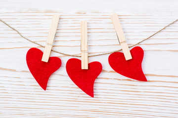 Three red hearts are piled by clothespins on a rope on a white wooden background
