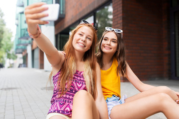 friendship, leisure and technology concept - smiling teenage girls taking selfie by smartphone on street in summer city