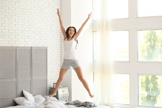 Beautiful young woman jumping on bed at home