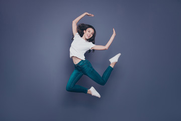Crazy adorable pretty lovely stylish nice cheerful dreamy curly-haired brunette girl in casual white t-shirt and jeans, fooling, flying in air, isolated on grey background