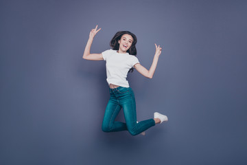 Adorable pretty lovely stylish nice cheerful dreamy curly-haired brunette girl in casual white t-shirt and jeans, flying in air, showing double v-sign, isolated on grey background